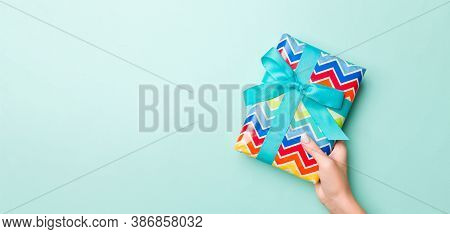 Woman Hands Give Wrapped Christmas Or Other Holiday Handmade Present In Colored Paper. Present Box,