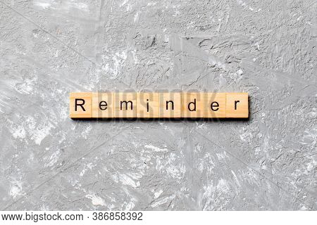 Reminder Word Written On Wood Block. Reminder Text On Cement Table For Your Desing, Concept