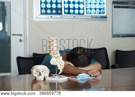 An Asian Male Neurosurgeon Feels Tired And Sleeping In The Medical Office. Skull And Lumbar Spine Mo