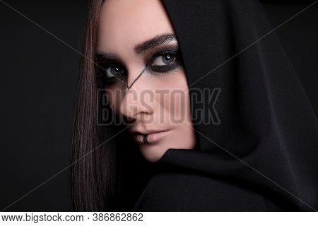 Mysterious Witch In Mantle With Hood On Black Background, Closeup