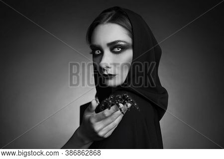 Mysterious Witch With Spooky Spider On Dark Background. Black And White Effect