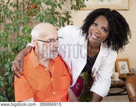 Horizontal Portrait Of An African American Medical Assistant Holding An Ederly Caucasian Man