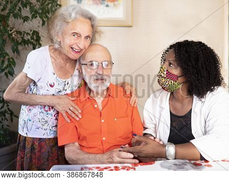 Horizontal Portrait Of An African American Medical Assistant Helping An Ederly Couple At Home In Tim