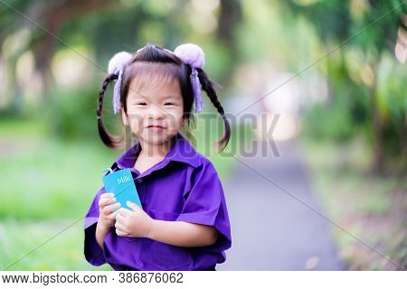 A Purple Dress Girl Stands Holding Blue Milk Carton Or Juice Box. Cute Child Sweet Smile. Children D