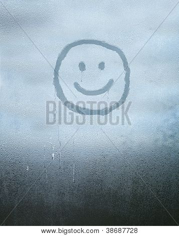 Smile face drawn over condensed glass