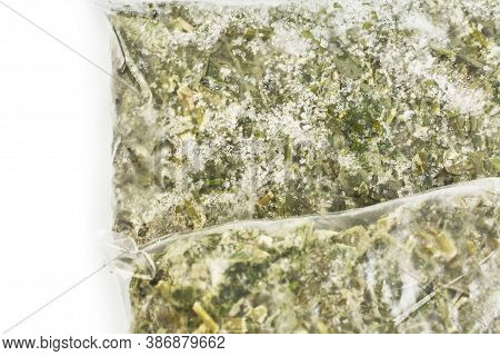 Packaged And Sliced ​​green Sorrel. Frozen Greens Isolated On A White Background. Preparation Of Foo