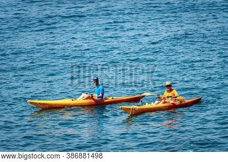 Tellaro, Italy - July 23, 2020: Two Men (one Young Adult And One Mature) Aboard Their Kayaks, Paddli