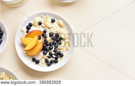 Oatmeal Porridge With Peach Slices, Almond And Wild Blueberries In Bowl Over Light Stone Background
