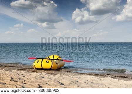 Yellow packraft rubber boat with red padle on a sea coast. Packrafting. Active lifestile concept
