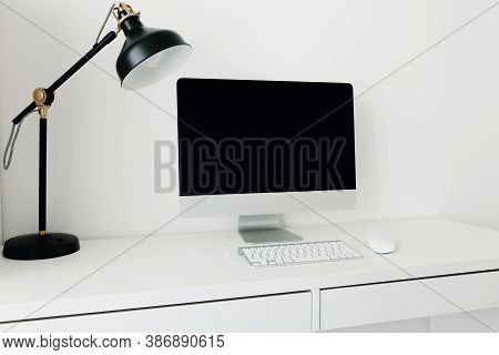 White Desktop With Black Monitor And Desk Lamp. Workplace Concept. Mockup Blank Computer Screen With