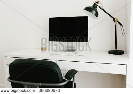 White Work Desk With Black Monitor, Desk Lamp And Chair. Workplace Concept. Minimalism In The Interi
