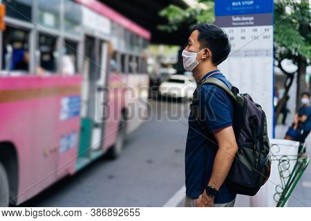 Mid Adult Asian Man Wearing Protective Face Covering, Waiting To Catch A Bus During The Pandemic, On