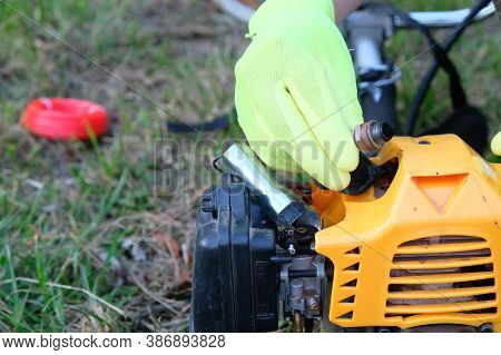 Hand Holds  Faulty Spark Plug On Background Of Grass Trimmer, Repair, Maintenance Of Household Tools
