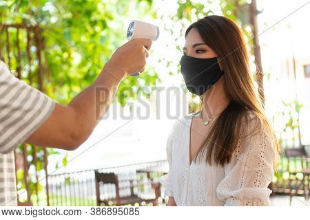 Close Up Hand Using Medical Digital Infrared Thermometer On Young Woman In Face Mask To Check And Mo