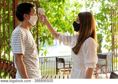 Young Woman Using Medical Digital Infrared Thermometer On A Young Man In Face Mask To Check And Moni