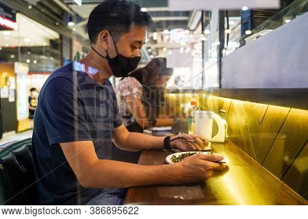 Asian Man Eating Lunch Separated With Acrylic Partition. Customers Having Dinner At Restaurant With