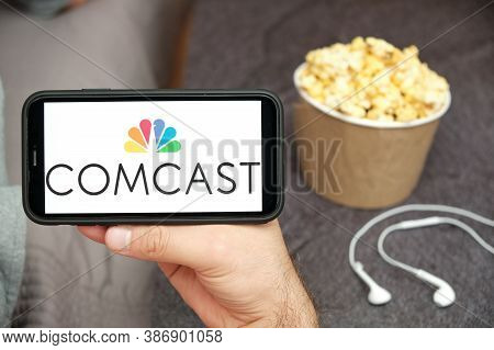 Comcast Logo On The Mobile Phone Screen With Popcorn Box And Apple Earpods On The Background. Leisur