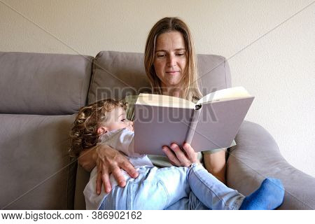 Mother Breastfeeds Her Child While Reading A Relaxed Book.