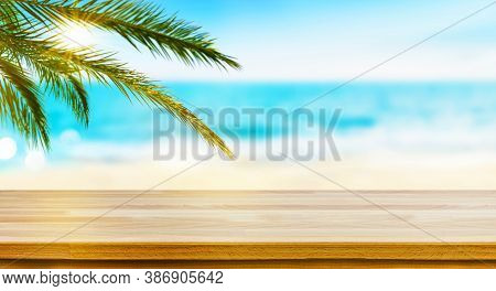 Wood Table Top On Tropical Sea, Sand Beach And Palm Leaves Background. Mockup For Display Your Produ