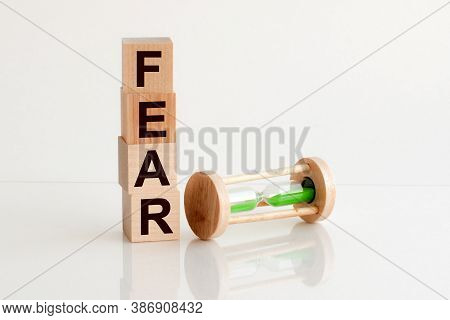 Close-up Of An Hourglass Next To Wooden Blocks With The Text Fear