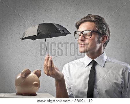 Businessman protecting a piggy with a little black umbrella
