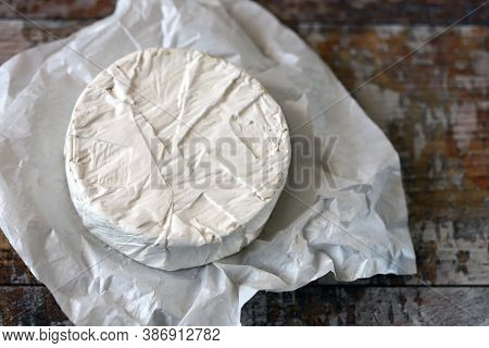 Round Camembert Cheese In Paper. Fresh Camembert Cheese.
