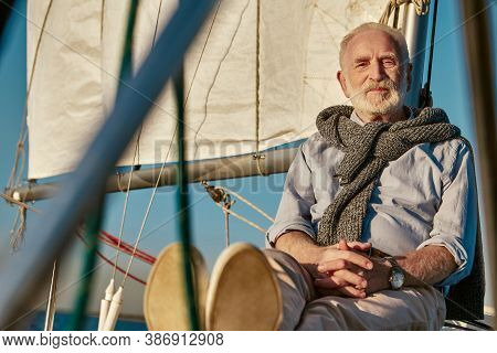 Sailing Man. Portrait Of A Relaxed Senior Man Sitting On The Side Of His Sailboat Or Yacht Deck Floa