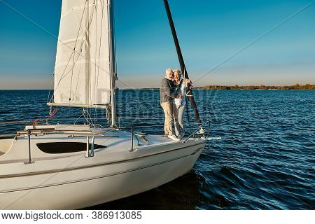 Boat Trip. Happy Senior Man And Woman Hugging And Enjoying Amazing View While Standing On The Side O