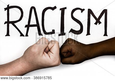 White And Black Hands Collide With Fists. Racial Conflicts, Racism And Ethnic Discrimination. Americ