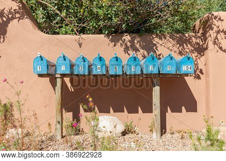 Santa Fe Usa - September 17 2015; Row Of Blue Letterboxes Shadows On Exterior Boundary Wall In Puebl