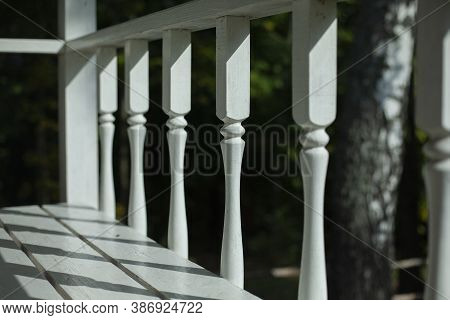 Balusters On The Veranda. The Railings Are White. Decorative Element. Wooden Details Of The Architec