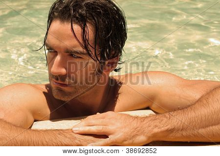 Detailed portrait of a beautiful male model in swimming pool