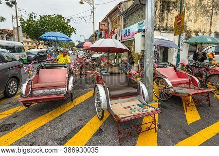 George Town, Penang, Malaysia - December 1, 2019: Street Life Of Trishaw Drivers Or Rickshaws In Geo