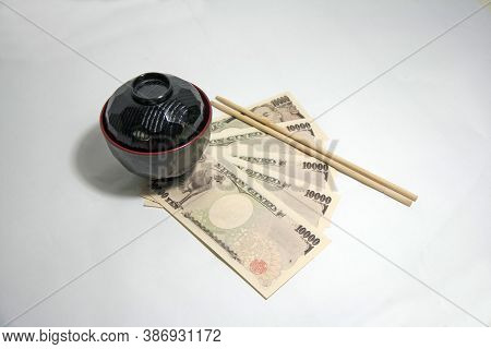 Black Color Red Edge Miso Soup Bowl And Wooden Chopsticks With Yen Banknotes Of Japan On The White B