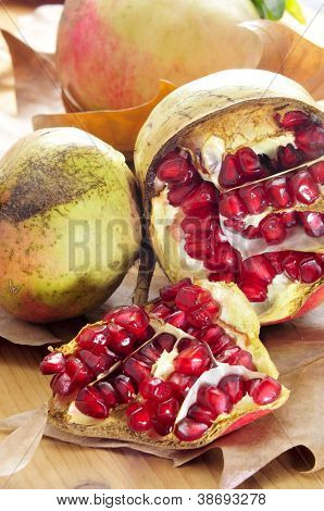 some pomegranate fruits and arils on an autumn background
