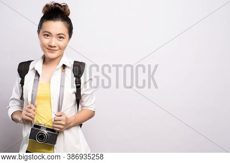Happy Woman Holding Camera Over Background And Looking At Camera