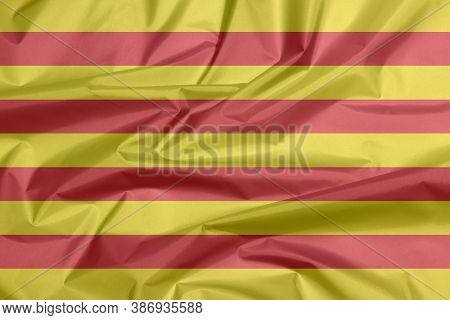 Fabric Flag Of Catalonia. Crease Of Catalunya Flag Background, The Red Stripe On Golden Background.