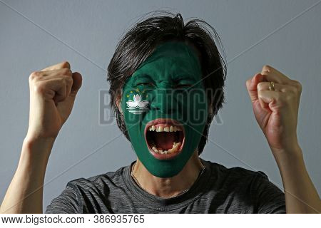 Cheerful Portrait Of A Man With The Flag Of The Macau Painted On His Face On Grey Background. The Co