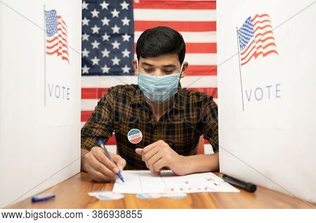 Young Man In Medical Mask Busy Inside The Polling Booth With Us Flag As Background - Concept Of In P