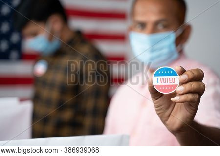 Close Up Of Hands, Man In Medical Mask Showing I Voted Sticker At Polling Booth With Us Flag As Back