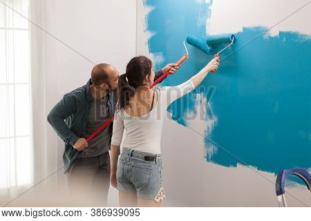 Wife Helps Her Husband To Renovate Using Rollers With Blue Paint. Home During Renovation, Decoration