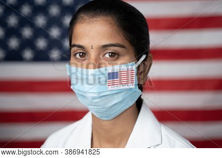 Close Up Face Of Girl With I Voted By Main Sticker On Her Medical Mask With Us Flag As Background -