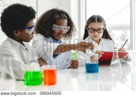 Group Of Teenage Cute Little Students Child Learning Research And Doing A Chemical Experiment While