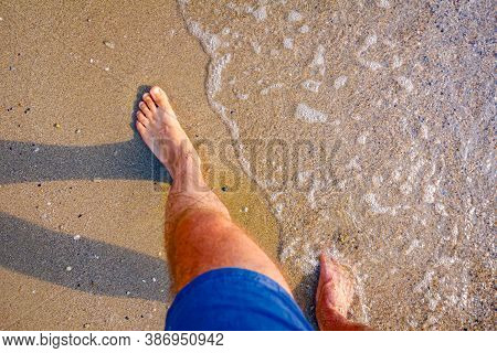 Barefoot Tourist Is Enjoying In Peaceful Walk, Relaxation On The Sandy Beach, Walking Through Shallo