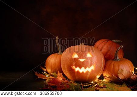 Halloween Pumpkins Over Autumnal Leaves And Glowing Garland On Dark Background. Illuminated Carved P