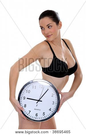 Woman in her underwear holding a large clock
