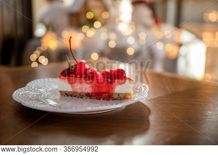 Slice Of Strawberry Cheesecake With Biscuit Layer, Cherry And Jam On White Plate At Restaurant