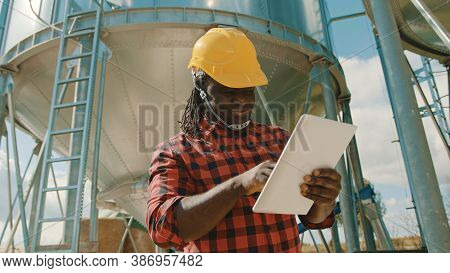 Young Handsome African Man, Engineer With Safety Helmet Using Tablet In Front Of Silo System. High Q