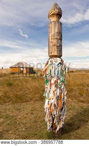 The Close-up Pagan Symbol With Sacred Colored Ribbons In The Steppe Of Khakassia. Yurt On The Backgr