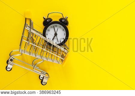 Alarm Clock In Mini Shopping Cart On Yellow Background. Buying, Time, Sale Concept. Flat Lay, Top Vi